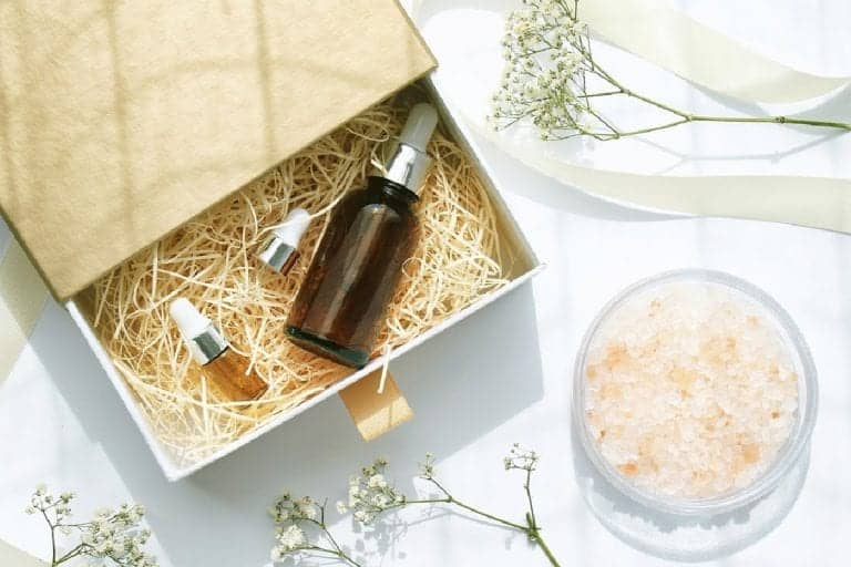 Facial serum, bath salts, and botanicals setting inside and around a gift box