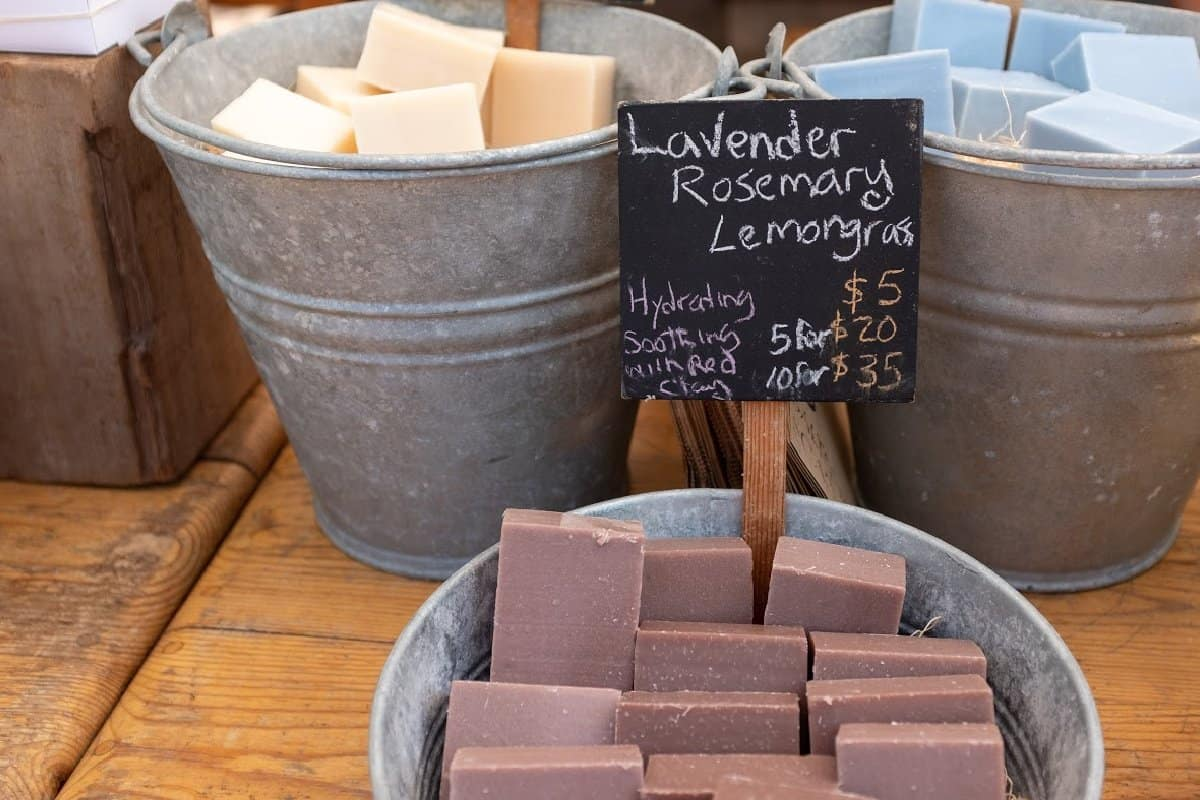 Handmade soaps in a tub with a sign showing prices.