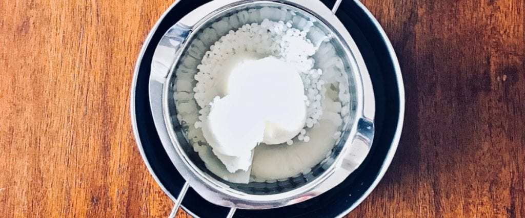 Adding organic beeswax, shea butter, and coconut oil to the double boiler to make organic lip balm.