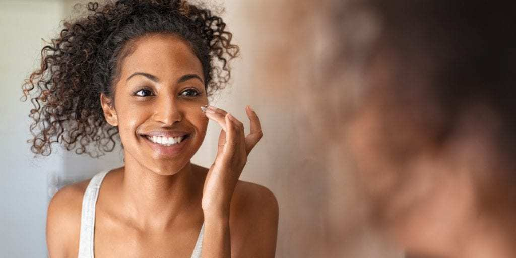 Woman applying anti-aging cream to her face.