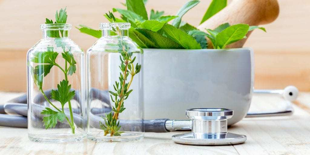 Herbs in glass bottles next to a doctors stethoscope to represent natural alternatives to traditional healthcare.