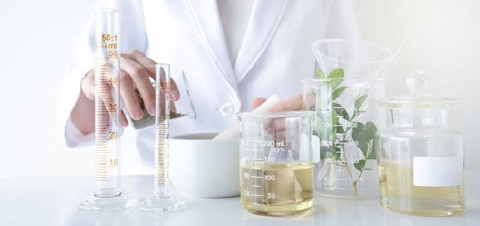Person making natural skin care products with carrier oils and herbs with glass beakers wearing a lab coat